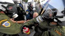 Anti-riot police try to detain a demonstrator in Thessaloniki, northern Greece. (ARIS MESSINIS/AFP/Getty Images)
