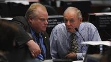 Toronto mayor Rob Ford converses with deputy mayor Doug Holiday during debate over the LRT transit issue at Toronto city hall on March 21, 2012. (Fred Lum/The Globe and Mail/Fred Lum/The Globe and Mail)