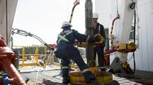 Employees work on an Alberta oil well partly owned by Cenovus Energy. (Brent Lewin/Bloomberg)
