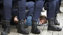 Riot police apprehend a protester during a general strike in Valencia, Spain, Wednesday, Nov. 14, 2012. (Fernando Hernandez/AP)