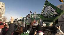 Fans cheer as the Saskatchewan Roughriders float passes them during the Grey Cup parade on Tuesday November 26, 2013 in Regina. The Saskatchewan Roughriders defeated the Hamilton Tiger-Cats 45-23 in the 101st CFL Grey Cup. (Liam Richards/THE CANADIAN PRESS)