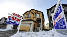 For sale signs in front of homes in Calgary. (TODD KOROL FOR THE GLOBE AND MAIL)