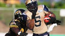 Winnipeg Blue Bombers' Chad Simpson, right, is tackled by Hamilton Tiger-Cats' Jamall Johnson during first half CFL action in Guelph, Ont., July 13, 2013. Chad Simpson knows the one way to stop more heads from rolling is for the floundering Blue Bombers to win a football game. (Aaron Lynett/THE CANADIAN PRESS)