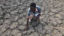 In this photo taken Sunday Jan. 29, 2016, Last Zimaniwa feels the broken ground at a spot which is usually a reliable water source that has dried up due to lack of rains in the village of Chivi , Zimbabwe. Zimbabwean president Robert Mugabe has declared a state of disaster as the country struggles to deal with a drought afflicting the region. (AP Photo/Tsvangirayi Mukwazhi)