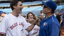 Liberal Leader Justin Trudeau shares a laugh with Toronto Blue Jays' head coach John Gibbons as wife Sophie looks on during batting practice on Friday, September 4, 2015 in Toronto. (Paul Chiasson/The Canadian Press)