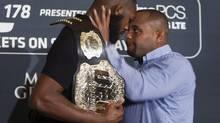 Challenger Daniel Cormier prepares to shove UFC light heavyweight champion Jon Jones during a UFC press conference to promote UFC 178 (Steve Marcus/AP)