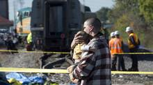 A man walks past a derailed train holding a young child. Wednesday September 18, 2013 in Ottawa. (Adrian Wyld/THE CANADIAN PRESS)