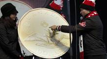 Steve Podborski, right, Chef de Mission for Canada at the 2014 Winter Olympics, inspects the newly unveiled 'LuckyLoonie' during a send-off party for Canada's Sochi bound Olympic athletes in Banff, Alta., Saturday, Jan. 11, 2014. (Jeff McIntosh/The Canadian Press)