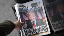 A man picks up a copy of London's Evening Standard newspaper featuring a photograph and story about U.S President-elect Donald Trump on the front page. (Carl Court/Getty Images)
