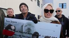 """actress Pamela Anderson and Sam Simon (left), producer of """"The Simpsons, """" talk to media outside the Canadian Sealers Association in St. John's, N.L., Tuesday, Dec.17, 2013. They attempted to deliver a letter with a million-dollar cheque to end the annual commercial seal hunt to the association but the office remained closed. (Paul Daly/CP)"""