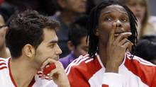 Toronto Raptors guard Jose Calderon and Chris Bosh (R) watch play from the bench during the second half of their NBA basketball game against the Philadelphia 76ers in Toronto March 7, 2010. REUTERS/Mike Cassese (MIKE CASSESE)