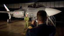 A Canadian Forces pilot has his picture taken in front of a F-35 Strike Fighter mock-up before a news conference in Ottawa on July 16, 2010. (Adrian Wyld/THE CANADIAN PRESS)