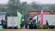 North Korean soldiers stand guard near Chinese trucks as labourers work for the preparation of the ground breaking ceremony of an industrial complex on Hwanggumpyong Island, near the North Korean town of Sinuiju and the Chinese border city of Dandong, on Tuesday, June 7, 2011. The island is planned to be developed by the joint efforts from China and North Korea into a center for tourism, logistics and manufacturing. (JACKY CHEN/JACKY CHEN/REUTERS)