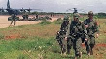 Members of the Canadian Airborne Regiment get into position as they arrive to assume responsibility for the airport at Bali Dogle, Somalia, on December 15, 1992. (Andrew Vaughan/Canadian Press)