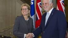 Ontario Premier Kathleen Wynne walks to meet Quebec Premier Philippe Couillard Thursday, August 21, 2014 at the premier's office in Quebec City. (Clement Allard/The Canadian Press)