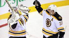 Boston Bruins goalie Tim Thomas (30) celebrates with teammate Patrice Bergeron after defeating the Montreal Canadiens 1-0 in National Hockey League action Monday, November 21, 2011 in Montreal. (Ryan Remiorz/THE CANADIAN PRESS)