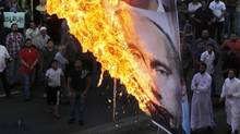 Protesters chant slogans against the Syrian regime and Russia's support of President Bashar Assad as they burn a banner depicting Assad, top, his brother, Maher Assad and Russian President Vladimir Putin, bottom, in the southern port city of Sidon, in Lebanon, Sunday, June 17, 2012. (MOHAMMED ZAATARI/AP)