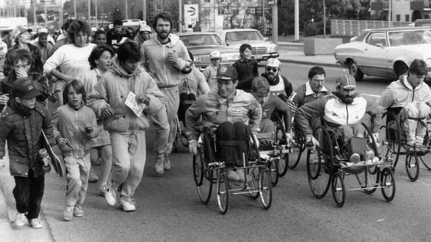 Rick Hansen, with a few other wheelchair athletes and small crowd of runners makes his way through a Toronto street on Nov. 2, 1986. Mr. Hansen is on the Canadian leg of his round-the-world trek to raise money for spinal cord research. (EDWARD REGAN/THE GLOBE AND MAIL)