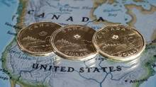 Canadian dollar coins are displayed on a map of North America. (Paul Chiass/The Canadian Press)