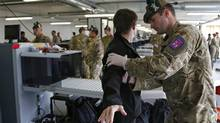 An unidentified person is searched by British military personnel at a security check point on arrival at the Olympic Park for the 2012 Summer Olympics, Monday, July 16, 2012, in London. (Jae Hong/AP)