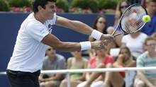Milos Raonic, from Canada,hits a return during a match against John Isner, of the United States, at the Western & Southern Open tennis tournament, Thursday, Aug. 15, 2013, in Mason, Ohio. Isner won 7-6 (5), 6-4. (Al Behrman/AP)