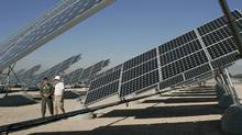 In this 2008 file photo, Col. Dave Belote (L), commander of Nellis Air Force Base, and Eric Vander Leest, a photovoltaic system technician for SunPower Corp., walk through an array of solar photovoltaic panels at the base in Las Vegas, Nevada. (STEVE MARCUS/REUTERS)