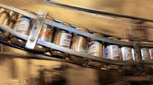 Cans of Miller High Life roll along the production line at the Miller Brewing plant in Milwaukee, Wis., in this Dec. 23, 2003, file photo. (MORRY GASH/AP)