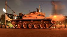 A man walks past an army tank from the republican guard in front of the presidential palace in Cairo Dec. 10, 2012. The country's foreign currency reserves have plunged by $21-billion (U.S.) since the uprising that ousted Hosni Mubarak in February 2011. (Mohamed Abd El Ghany/Reuters)