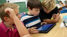 (L-R) Nicklaus O' Rourke,Noah Dobbiestamos and Owen Hakker play with an iPad at Monsignor Uyen Catholic School in Chatham, Ontario, October 18, 2010. (Geoff Robins For The Globe and Mail/Geoff Robins For The Globe and Mail)