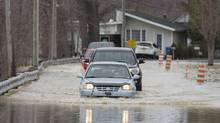 Cars move along a street in the town of Rigaud, Que., west of Montreal, on April 20, 2017, following flooding in the area. (Graham Hughes/THE CANADIAN PRESS)