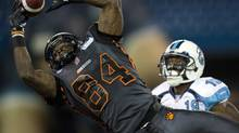 B.C. Lions' Emmanuel Arceneaux (84) dives to haul in a pass in front of Toronto Argonauts defensive back Jalil Carter (19) during first half CFL action in Toronto on Sunday August 17, 2014 (Frank Gunn/THE CANADIAN PRESS)
