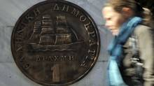 A woman walks by a monument presenting the last Greek drachma coin in Athens on Nov. 1. The drachma currency was used by Greece before the euro. Greek Prime Minister George Papandreou plunged the euro back into crisis and sent share prices into a tailspin on Oct. 31 with a shock announcement that he would put a hard-fought rescue deal to a referendum. (LOUISA GOULIAMAKI/LOUISA GOULIAMAKI/AFP/GETTY IMAGES)