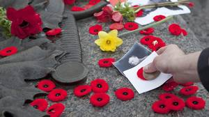 A person places a poppy and photo on the tomb of the Unknown Soldier at the National War Memorial following an End of an Era ceremony in Ottawa on Friday, April 9, 2010. The special ceremony honours those who fought in the First World War.