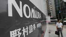 A man walks past a sign of Nomura Securities in Tokyo Sept. 6, 2012. Nomura Holdings Inc., Japan's biggest brokerage, said it will make cuts in its equities and investment banking businesses as it looks to chop $1-billion in costs. (KIM KYUNG-HOON/REUTERS)