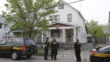 Sheriff deputies stand outside a house in Cleveland Tuesday, May 7, 2013, the day after three women who vanished a decade ago were found there. Amanda Berry, Gina DeJesus and Michelle Knight, who went missing separately about a decade ago, were found in the home just south of downtown Cleveland and likely had been tied up during years of captivity, said police, who arrested three brothers.