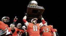 Laval Rouge et Or players Guillaume Rioux (11), Pascal Lochard (L), Vincent Plante (36) and Pierre Lavertu (R) celebrate with the trophy after defeating the Calgary Dinos to win the Vanier Cup University Championship football game in Quebec City, Quebec, November 23, 2013. (Reuters)