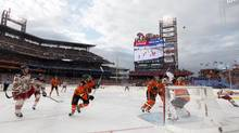 Members of the Philadelphia Flyers and the New York Rangers follow the flying puck during the first period in the NHL Winter Classic hockey game in Philadelphia, January 2, 2012. With no end in sight to the lockout, the showcase event may be cancelled, which could kill the NHL's U.S. momentum. (GARY HERSHORN/REUTERS)