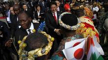 Japanese Prime Minister Shinzo Abe is welcomed Friday by local chiefs in Abidjan, Ivory Coast, at the start of his African tour. (LUC GNAGO/REUTERS)
