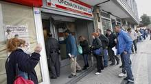 People stand in line to enter a government-run employment office in Madrid. (ANDREA COMAS/REUTERS)