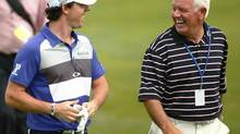 Rory McIlroy of Northern Ireland (L), laughs with his father, Gerry as they walk down the fairway during a practice round in preparation for this week's PGA Championship golf tournament at The Ocean Course on Kiawah Island, South Carolina, August 7, 2012. (© CHRIS KEANE / Reuters)