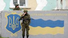 Russian servicemen stand guard behind a wall on which the Ukrainian national flag is painted at the Belbek Sevastopol International Airport in the Crimea region March 4, 2014. (VASILY FEDOSENKO/REUTERS)