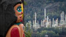 A totem pole on the Tsleil-Waututh First Nation, a gift from the Lummi Nation in Washington state, frames the Chevron Burnaby Oil Refinery in the distance after the totem was unveiled during a ceremony in North Vancouver, B.C., on Sept. 29, 2013. (Darryl Dyck/The Canadian Press)