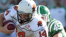 BC Lions quarterback Travis Lulay gets taken down on the play by Saskatchewan Roughriders linebacker Jerrell Freeman (bottom) and linebacker Mike McCullough during the first half of their CFL football game in Regina, Saskatchewan September 24, 2011. REUTERS/David Stobbe (DAVID STOBBE)