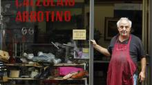 Cobbler Vincesco Scofano, 63, poses in front of his shop in Milan Oct. 9, 2012. Thousands of small shops and businesses have closed up over the past few years of Italy's economic downturn. (ALESSANDRO GAROFALO/REUTERS)