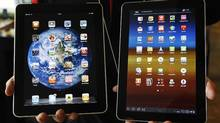 An employee of South Korean mobile carrier KT holds a Samsung Electronics' Galaxy Tab 10.1 tablet (R) and Apple Inc's iPad tablet as he poses for photos at a registration desk at KT's headquarters in Seoul August 10, 2011. (JO YONG-HAK/REUTERS)