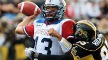 Montreal Alouettes quarterback Anthony Calvillo tries to throw a pass as he is hit by Hamitlon Tiger-Cats Justin Hickman during first-half. THE CANADIAN PRESS/Dave Chidley (Dave Chidley/CANADIAN PRESS)