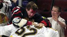 In this Oct. 28, 2001, file photo, Chicago Blackhawks' Bob Probert, left, and Boston Bruins' Andrei Nazarov mix it up along the boards during a first period fight in Chicago. Enforcers, goons, whatever you want to call them, players like Bob Probert and Derek Boogaard made careers from dishing out and taking punishing hits. That job is sure to come under added scrutiny after thesudden death of Boogaard, five months after he suffered a season-ending concussion. (Fred Jewell/AP)