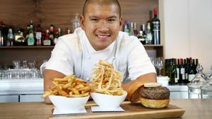 Chef David Lee with a Stilton brisket beef burger with fois gras, pommes frites, and onion rings.