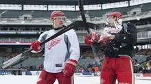 Detroit Red Wings' Justin Abdelkader, left, tosses some snow into the face of teammate Brendan Smith as they walk out onto the ice to the outdoor hockey rink for practice at Comerica Park, home of the Detroit Tigers baseball team, Wednesday, Dec. 18, 2013, in Detroit. (David Guralnick/AP)