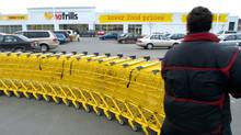A worker drags a row of shopping carts from the parking lot toward the front door of a Mississauga No Frills grocery store. (J.P. Moczulski)